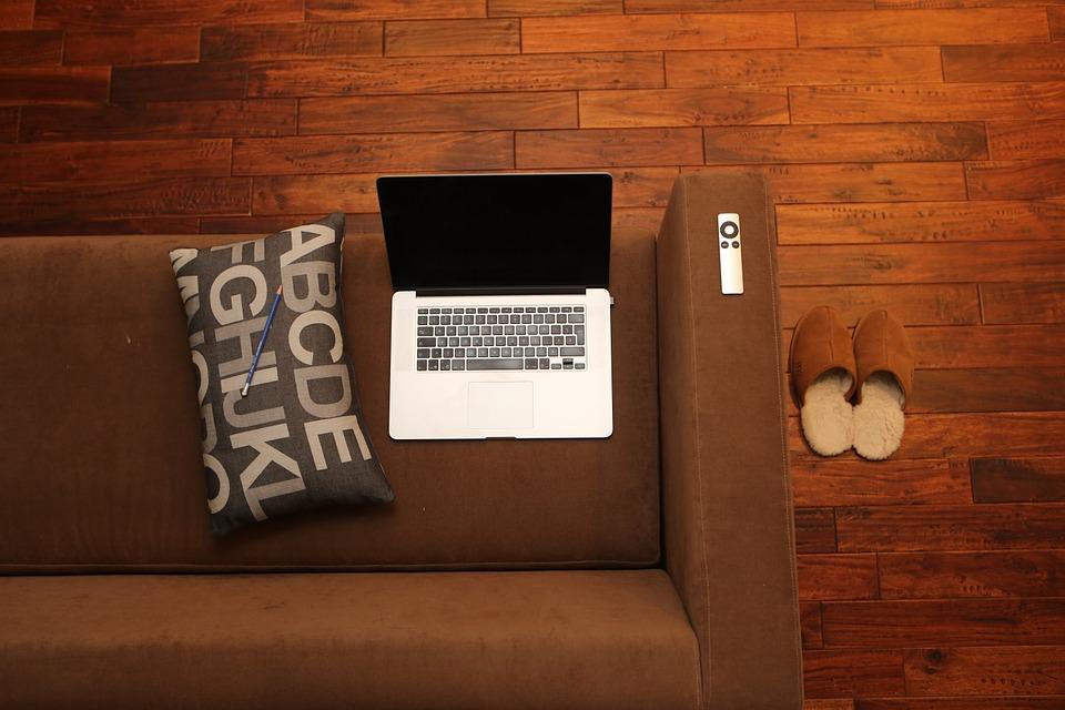 Ordenador sobre el sofá junto a zapatillas de estar por casa