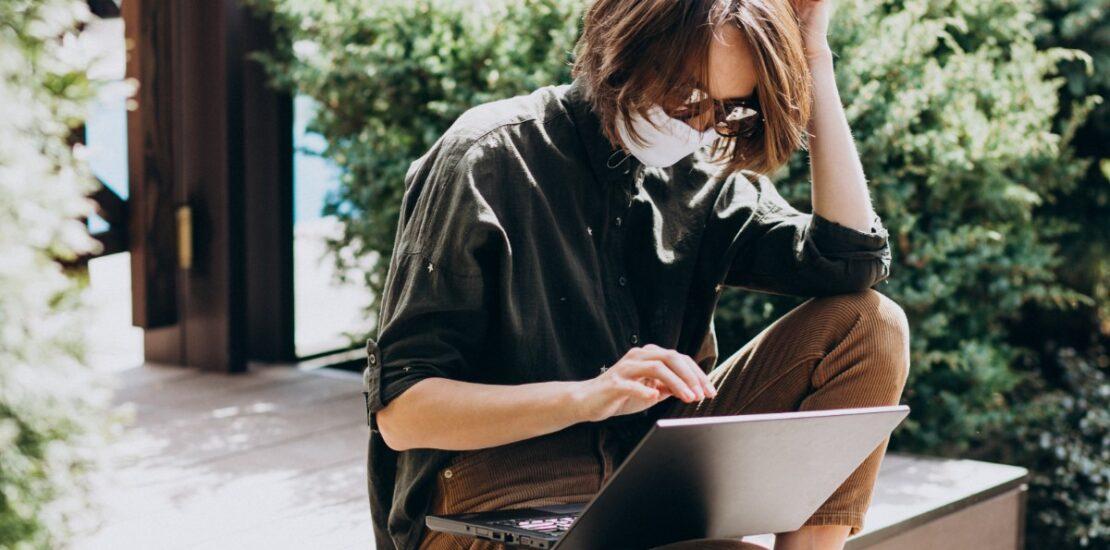 Mujer con mascarilla buscando en su portátil